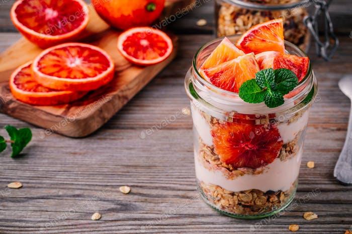 healthy breakfast  glass jar yoghurt parfait with homemade granola and blood orange