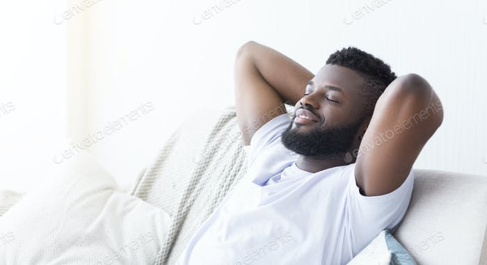 Happy african american guy enjoying free time at home