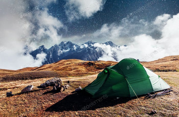Fantastic starry sky. Tent against the backdrop of snow-capped mountain peaks. The view from the