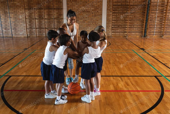 Front view of schoolkids and female coach forming hand stack at basketball court in school