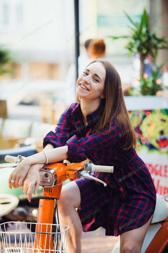 Portrait of pretty smiling girl on scooter