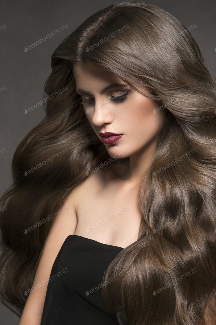 Beauty hair woman portrait long curly hairstyle fashion makeup healthy skin. Dark background.