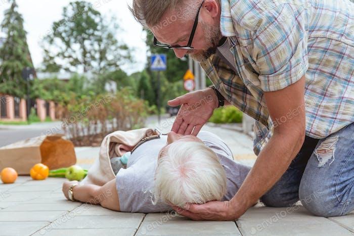 Erste Hilfe für ein Unfallopfer auf der Straße liegend