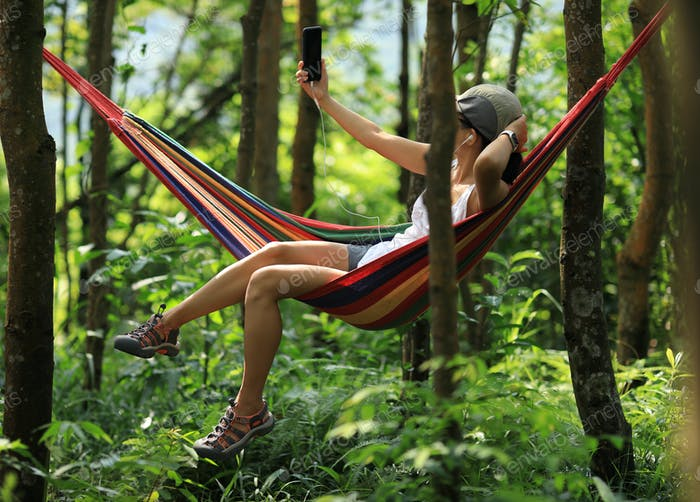 Woman relaxing in hammock and using smartphone in forest