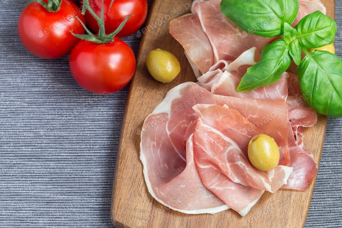 Prosciutto ham on wooden board with green olives, tomato and bas