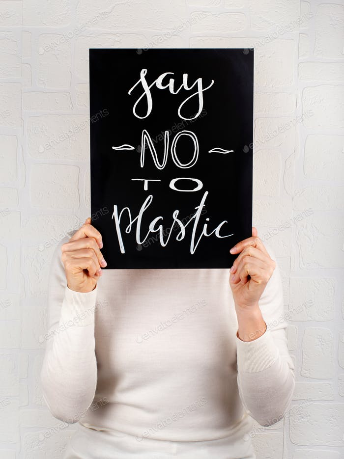 Woman keeping a small chalkboard with SAY NO TO PLASTIC lettering