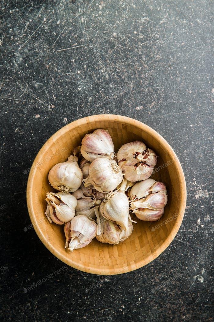 Fresh healthy garlic in wooden bowl.