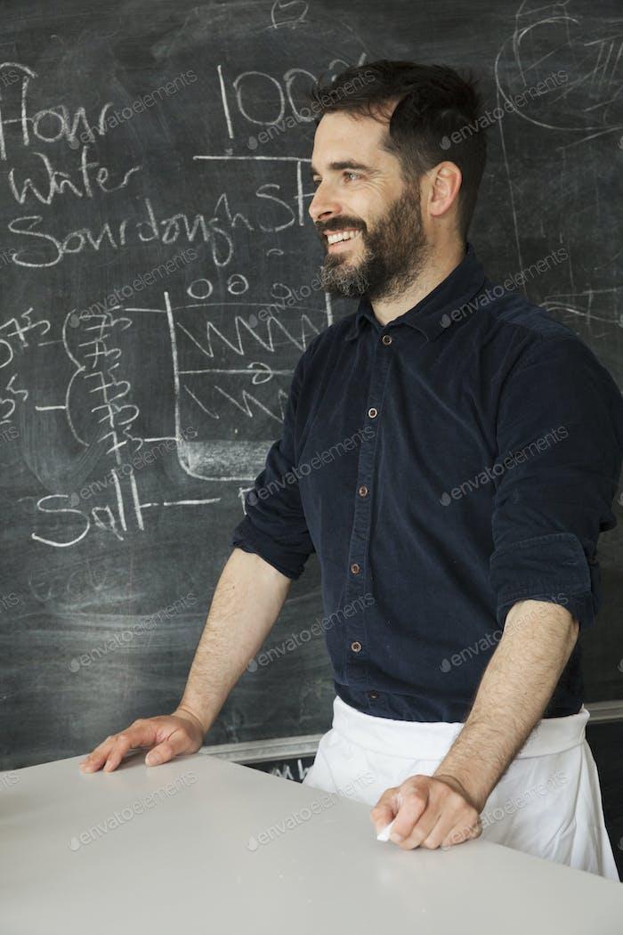 Baker steht vor einer Tafel mit einem Rezept für Brot darauf geschrieben.