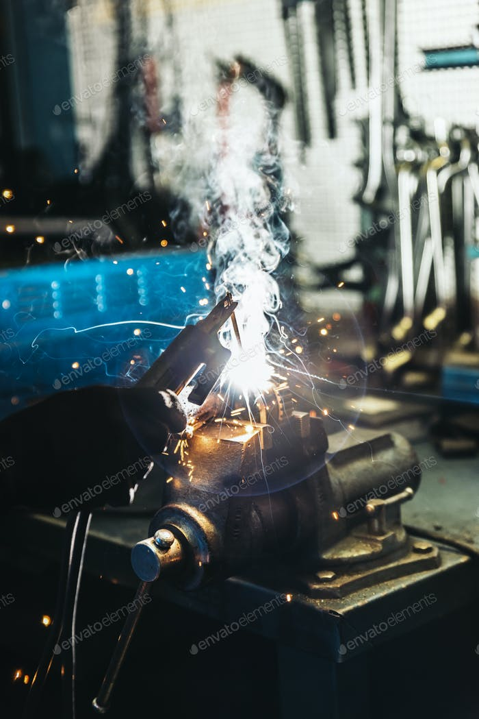 Mechanic man welding metal material in garage