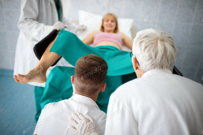 Obstetricians assisting in the hospital woman in labor pushes to give birth