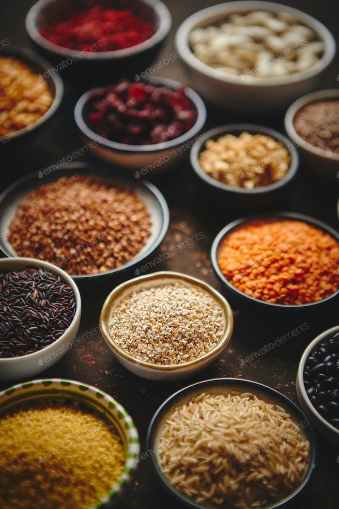Verschiedene Superfoods in kleinen Schalen auf dunklem rostigen Hintergrund