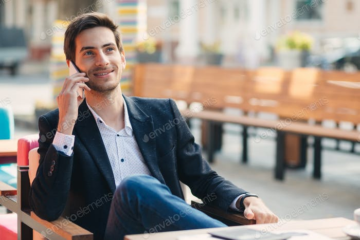 Portrait of young smiling businessman talking on the phone