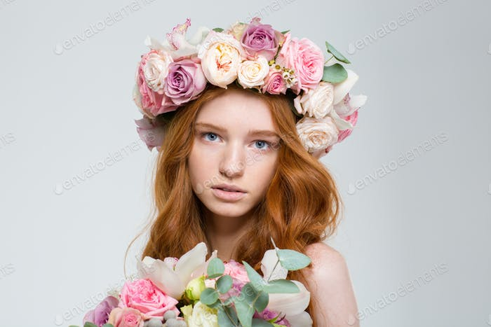 Tender female in roses wreath holding bouquet of flowers