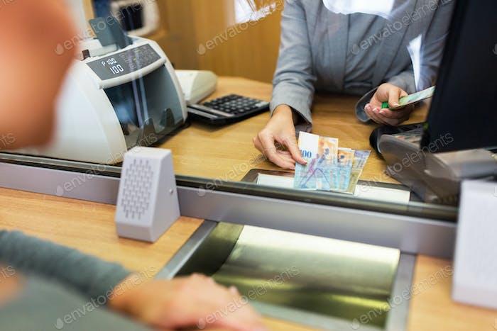 empleado que cuenta dinero en efectivo en la oficina del banco