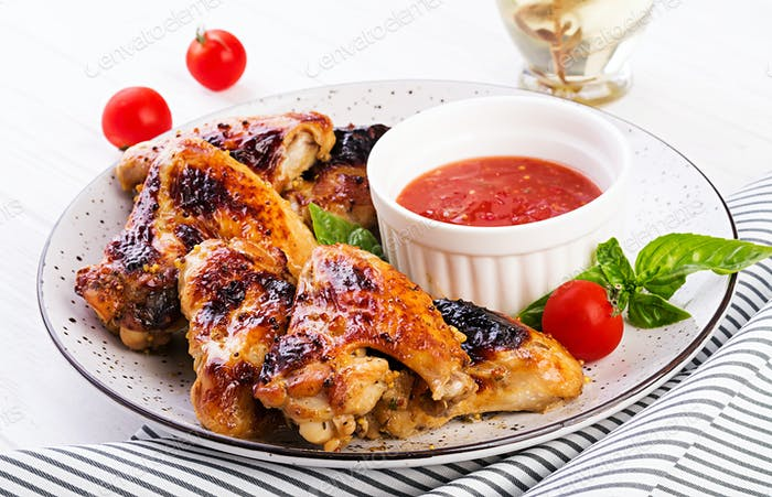Baked chicken wings in the Asian style and tomatoes sauce on plate.
