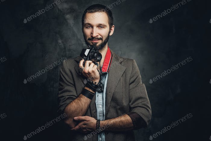 Man is posing for photographer with photo camera