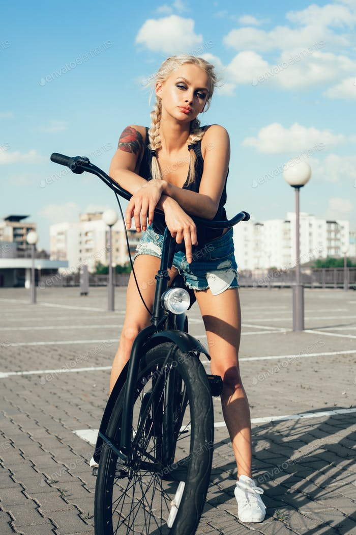 Pretty blonde woman with bicycle in city