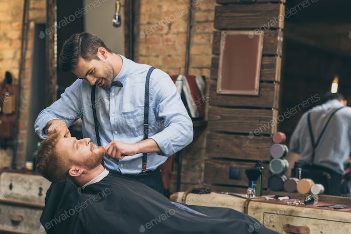 Male barber trimming customers beard in barber shop