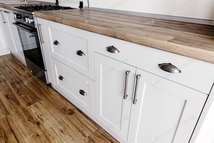 Close-up steel handles on modern stylish light grey kitchen interior