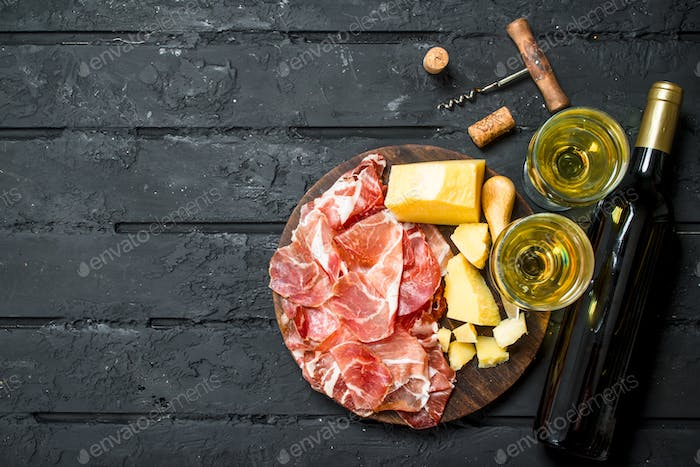 Antipasto background.Italian appetizers with white wine.
