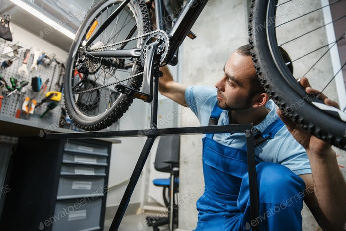 Bicycle repair, man checks the wheel for backlash
