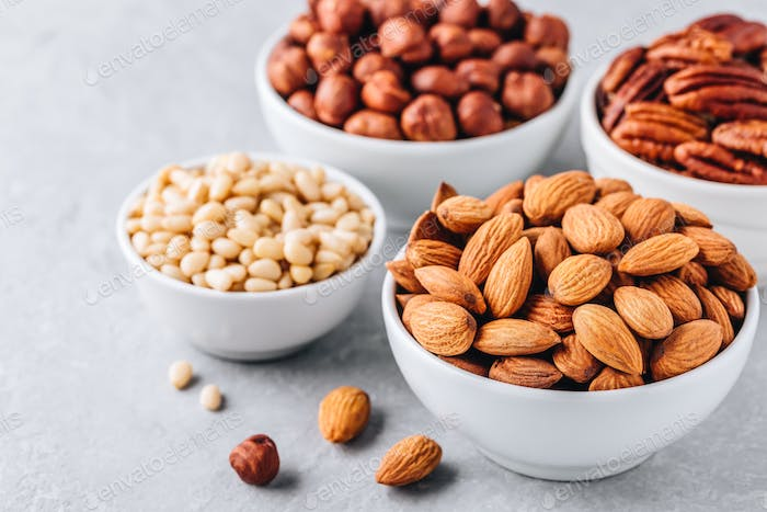 Almonds, pecans, pine nuts and hazelnuts in white bowls on grey background. Nuts mix.