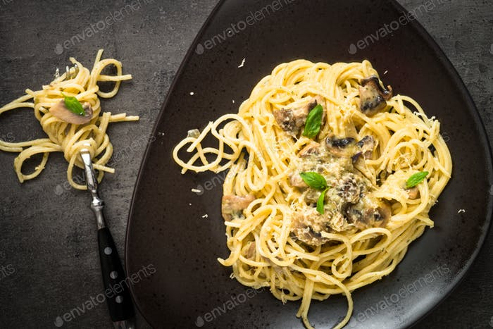 Pasta with mushrooms and white sause with basil.