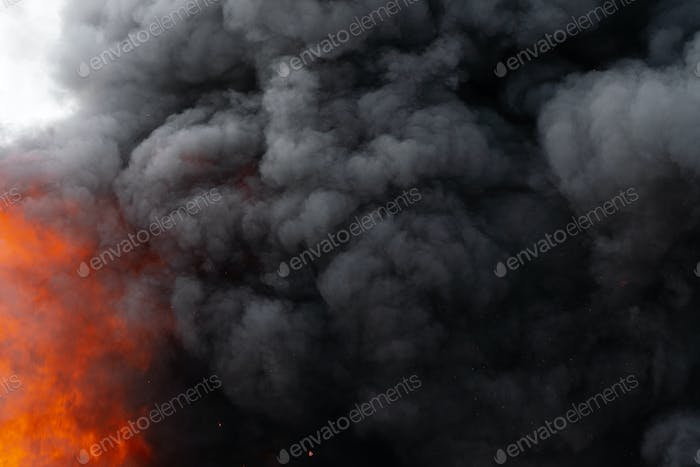 Flames of Red Fire and Motion Blur Clouds of Black Smoke Covered Sky