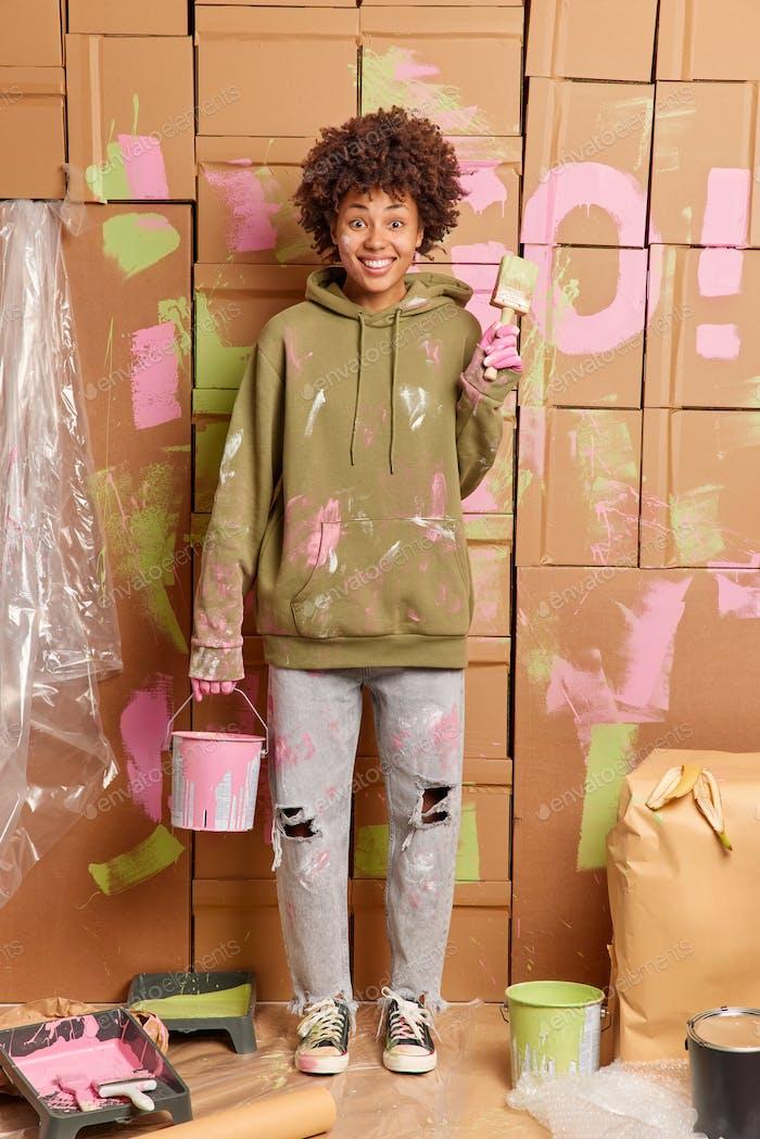 Концепция ремонта дома. Положительный женщина декоратор держит банку краски и кисти счастлив закончить