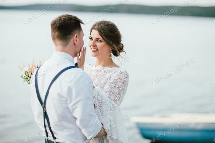 Happy newly married couple near lake