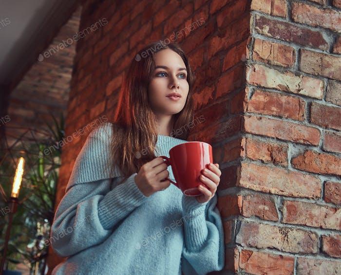 Eine sinnliche Brünette in einem grauen Pullover