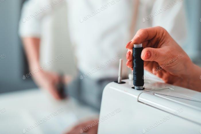 Professional dressmaker using sewing machine, close up