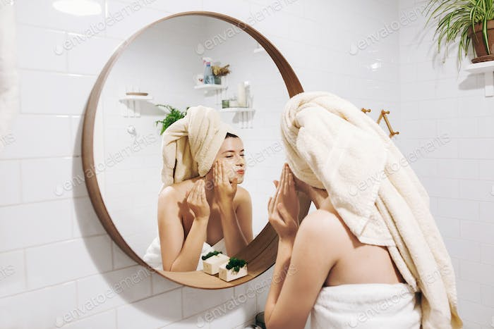 Young happy woman in towel applying organic face mask and looking at round mirror