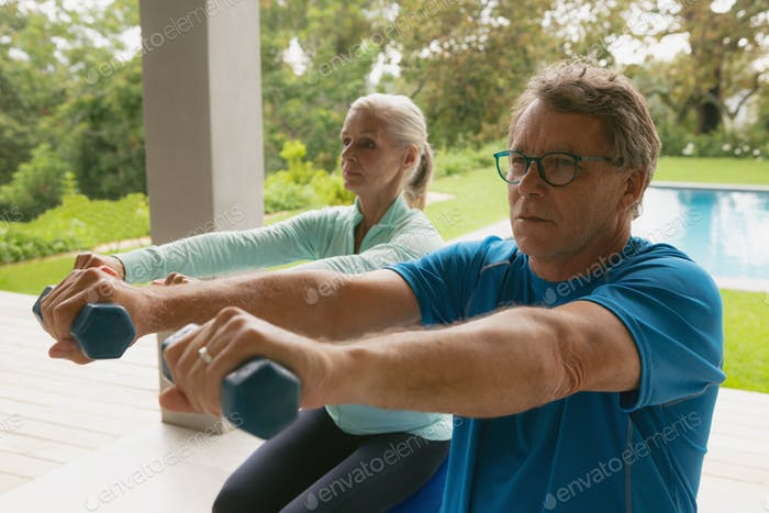 Front view of active senior Caucasian couple exercising with dumbbell in porch at home
