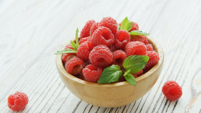 Bowl with raspberries and leaves