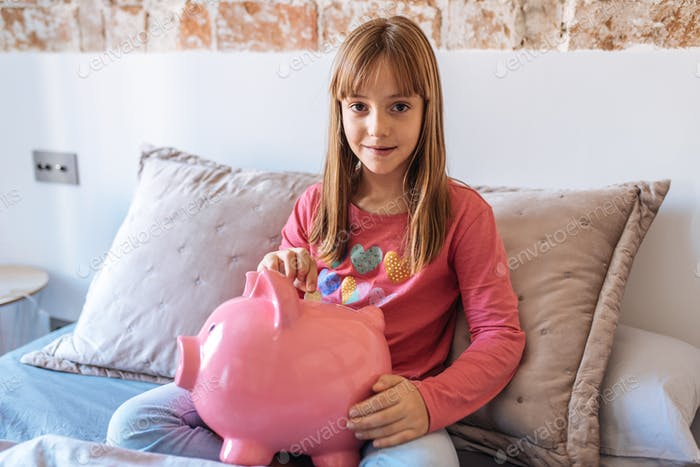 Portrait of a young cute little blonde girl sitting in the bed putting money on the piggy bank
