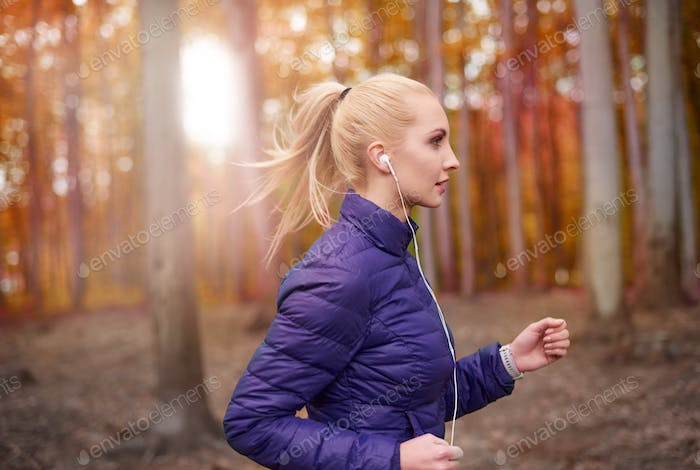 Woman focused on running in the woodland