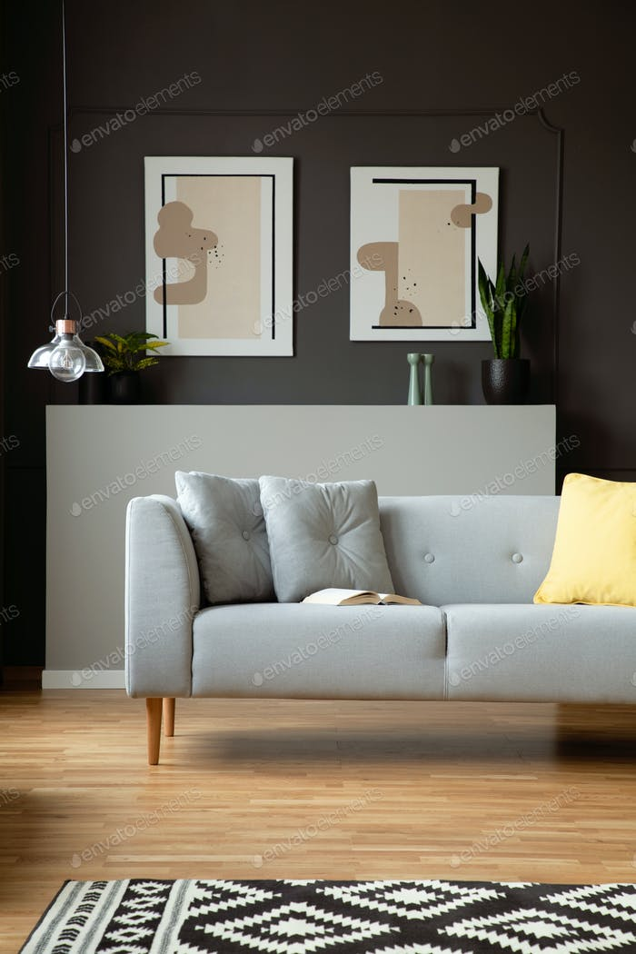 Couch with grey cushions next to lamp in living room interior wi