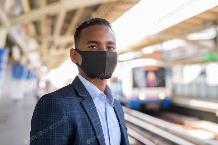 Young African businessman with mask for protection from corona virus outbreak thinking and waiting