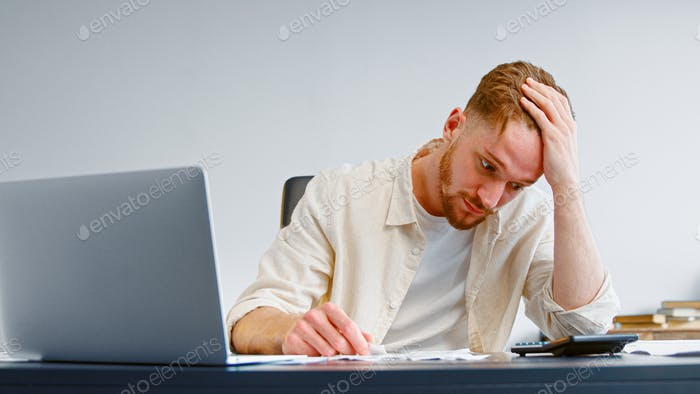 Concentrated and worried manager looks at paper checks and total sum on calculator