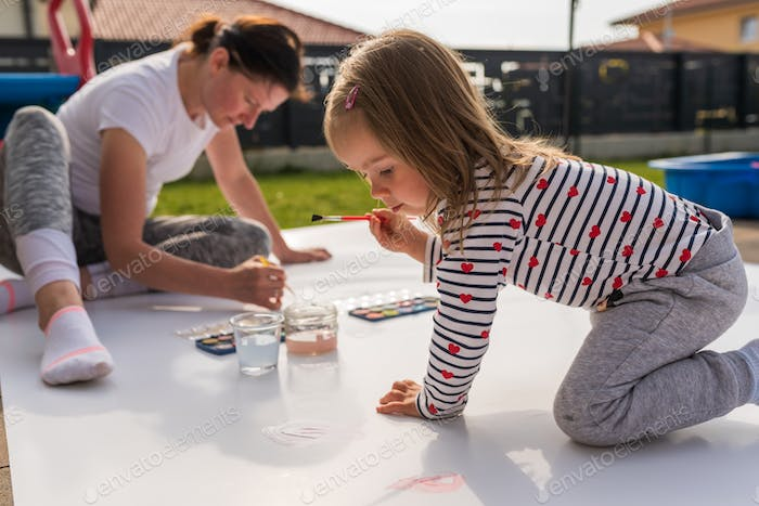 Child with mother painting with poster paint outdoors on the ground on big sheet of paper.