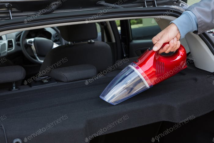 Auto service staff cleaning car with portable vacuum