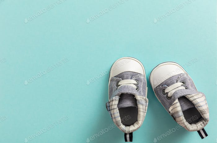 Baby boy shoes on pastel blue background