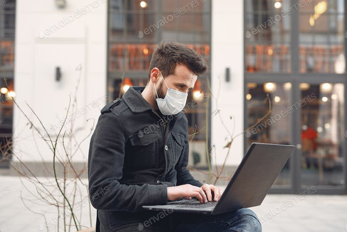 Man in a mask sitting in the city with a laptop