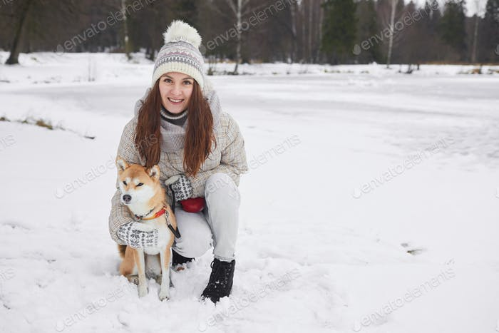 Young Woman Posing with Dog in Winter