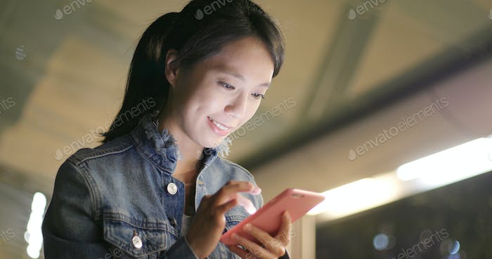 Woman looking at mobile phone at night