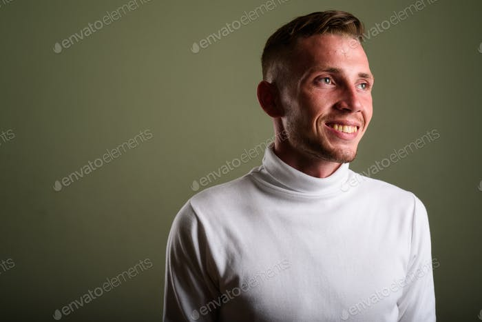 Young man wearing white turtleneck sweater against colored backg