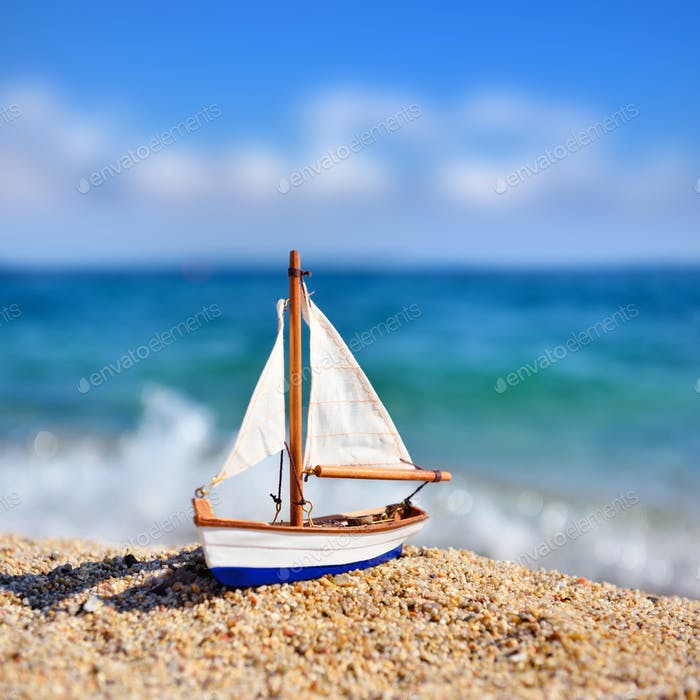 Miniature toy sailboat on the beach against the background of the sea and the blue sky