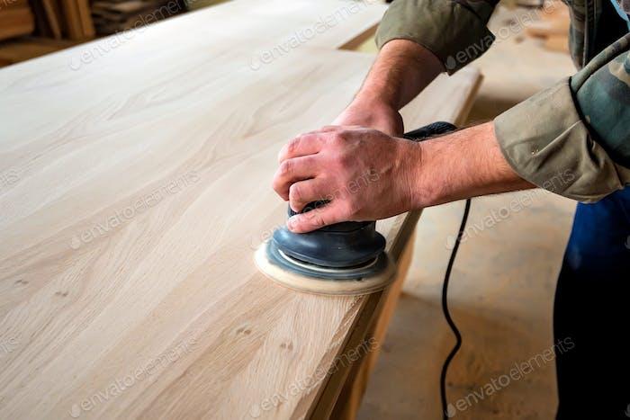 Man sanding wood with orbital sander in a workshop