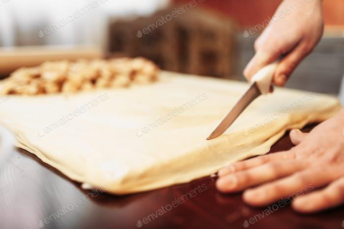 Männlicher Koch bereitet Apfelstrudel